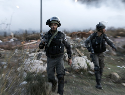 An Israeli border policeman looks on as he walks through tear gas fumes during clashes with Palestinian protesters near an Israeli checkpoint in the West Bank city of Ramallah on December 10, 2017, following the US president's controversial recognition of Jerusalem as Israel's capital. New protests flared in the Middle East and elsewhere over US President Donald Trump's December 6 declaration of Jerusalem as Israel's capital, a move that has drawn global condemnation and sparked days of unrest in the Palestinian territories. / AFP PHOTO