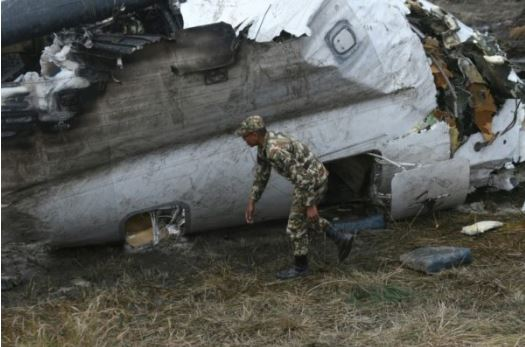 Rescuers cut apart the mangled and burned wreckage of the upturned Bangladeshi plane